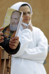 A pilgrim holds the picture of Padre Pio next to a nun during a Mass in San Giovanni Rotondo