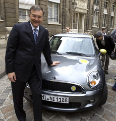 Chief Executive of German luxury carmaker BMW Norbert Reithofer poses in front of a BMW Mini-E electric car during a press event at the Transport Ministry in Paris