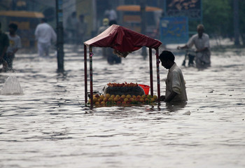 A Pakistani fruit vendor mans his stall at a flooded street after heavy downpour in Lahore.