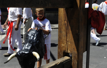 """A boy pushing a toy bull looks at a scarf left near the place where Spanish runner Daniel Jimeno was gored to death by Jandilla ranch fighting bull """"Capuchino""""  at the San Fermin festival in Pamplona."""
