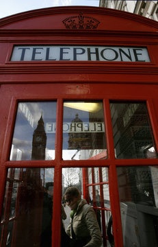 The Big Ben is seen reflected in the glass of a public telephone booth in central London