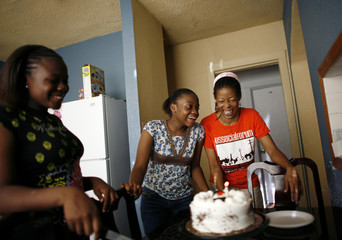 Paulette Richards enjoys a birthday cake with her granddaughters Lashaevia and Stephanie at their home in Miami's neighbourhood of Liberty City