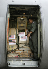 A serviceman from Malaysia's armed forces checks relief supplies donated by the Malaysian government at an airbase near Kuala Lumpur