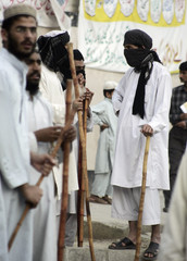 Pro-Taliban Islamist students hold bamboo sticks as they stand outside a mosque in Islamabad