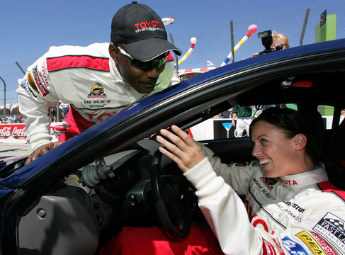 Karl Malone jumps on the windshield of Amanda Beard at the 29th Annual Pro/Celebrity Race.