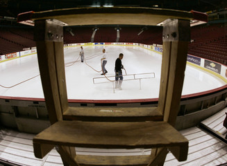 Workers are framed by a ladder as they prepare the ice at GM Place for the upcoming NHL season in ...