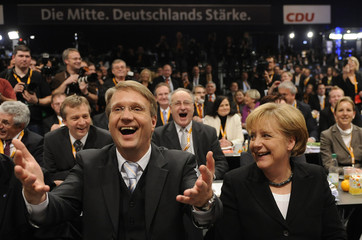 German Chancellor Merkel sits next to party general Pofalla as he reacts to her re-election as CDU leader at CDU party meeting in Stuttgart