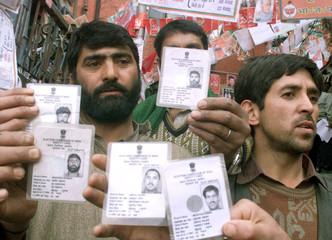 MUSLIM KASHMIRI MIGRANTS SHOW THEIR VOTER IDENTITY CARDS IN SHIMLA.