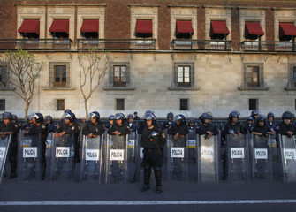 Police officers stand guard in front of the National Palace in Mexico City
