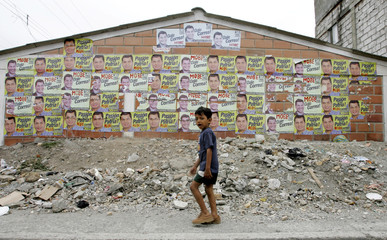 A child walks past electoral posters in support of leftist Presidential candidate Rafael Correa in El Recreo