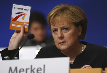 German Chancellor Merkel holds up a voting card during the party congress of her conservative Christian Democratic Union party CDU in Hanover