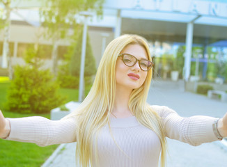 Selfie portrait of a beautiful girl in a beige dress and glasses during the day outdoors. The model is posing in front of the camera. The concept of a beautiful life.