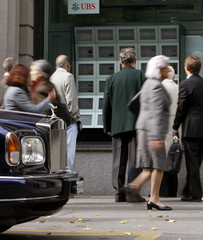 A Rolls Royce limousine is parked beside display showing the current stock prices at the office of Swiss bank UBS, in Zurich