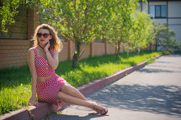Portrait young pinup style american girl on weekend in village farm. Stylish woman with necklace accessories in red suit and cat eye glasses on nature at outdoor