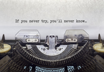 Vintage typewriter on white background with text If you never try, you'll never know.