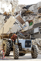 A man drives his tractor past the rubble of a collapsed house three days after an earthquake struck the Italian village of Onna