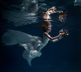 young girl in beautiful white dress posing underwater in the pool