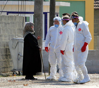 A woman talks to Turkish health experts in protective suits hunting poultry to cull to stop an outbreak of avian flu in the quarantined town of Kiziksa in Turkey