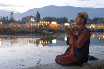 A KASHMIRI MOSLEM OFFERS EVENING PRAYER ON THE BANKS OF DAL LAKE.
