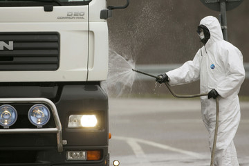 A soldier of the German armed forces Bundeswehr wears a protection suit as he cleans a truck before ..