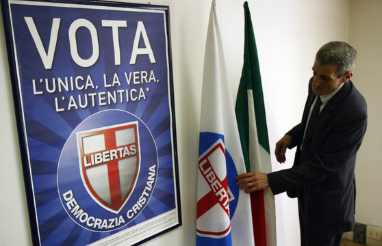 A man adjusts the flag of the Democrazia Cristiana party before of an interview with the secretary Giuseppe Pizza in his office in Rome