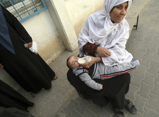 Palestinian woman feeds grandson in front of UN headquarters in Jabalya