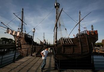Boy runs next to replica of caravel which Cristobal Colon used to discover America are berthed in La Rabida