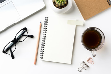 Business concept - Top view of white desktop background with notebook, coffee, smart phone, cactus and clip for mockup design