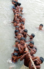 Bangladeshi children bathe while hanging onto the rope of a vessel on the bank of the Buriganga rive..