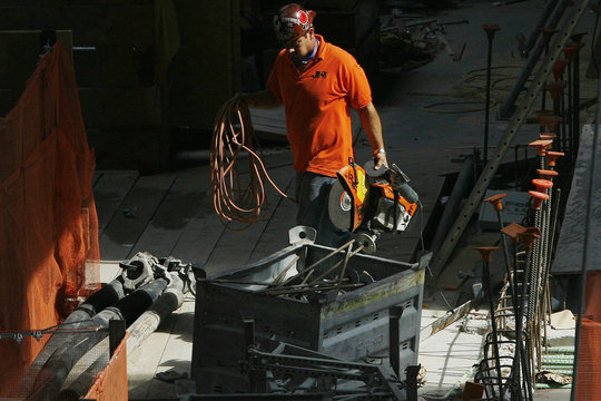 A worker carries tools while working at the World Trade Center construction site in New York