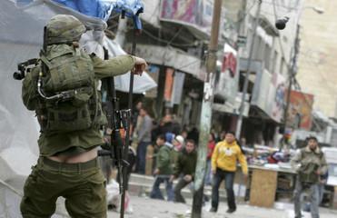 An Israeli soldier throws a stun grenade at Palestinian demonstrators in Hebron