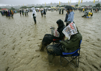 Revellers sit in the mud and rain as they listen to the Waterboys during the Glastonbury music festival