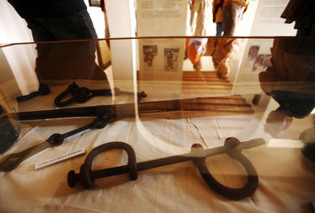 Visitors are reflected in a glass display case containing iron leg shackles at the House of Slaves museum on Goree Island near Senegal's capital Dakar
