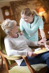 Nurse bringing breakfast to senior female patient
