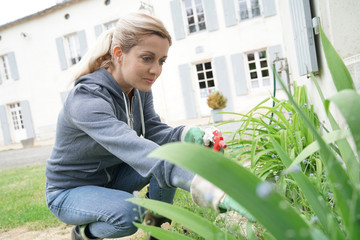 Woman in garden spraying insecticide over plants