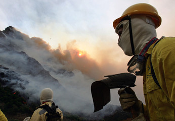Volunteer firemen prepare to fight a blaze on Table mountain in Cape Town, South Africa