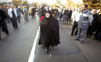 Iranian woman whose son was killed in plane crash tries to find his coffin during funeral ceremony in Tehran