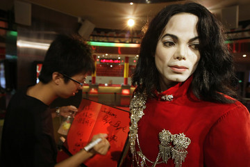"""A visitor writes """"Jackson bye bye """" on a condolence book next to a wax figure of Michael Jackson at Madame Tussauds Wax Museum in Shanghai"""