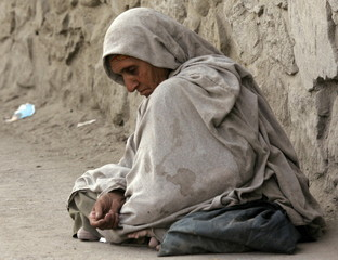An Afghan woman waits for alms in Kabul September 17, 2005. [Eleven people were killed in clashes ah..