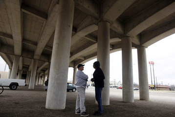 """Pastor Jimmy Dorrell speaks to a parishioner at the """"Church Under the Bridge"""" worship service in Waco"""