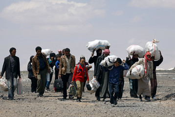 Internally displaced people who fled Raqqa city carry their belongings as they leave a camp in Ain Issa