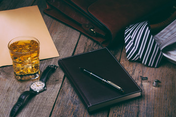 business accessories - notebook, pen, rich portfolio, watch, tie, glass of whiskey with ice on wooden background,