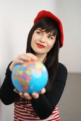 frau mit roter mütze hält eine weltkugel in der hand