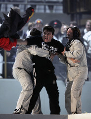 Protester is restrained during the speech by TOROC President Castellani during the closing ceremony  at the Winter Olympic Games