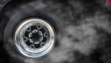 Isolated  sport car wheel with drifting and smoking on a black background