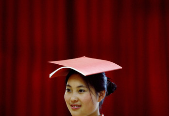 A student balances book on her head during etiquette training class at vocational school in Beijing