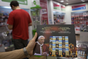 Postal worker shows special edition of stamps at post office  in Jerusalem