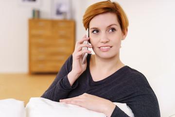 frau sitzt auf dem sofa und telefoniert mit ihrem handy