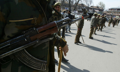 Indian policemen stand guard at a street in Srinagar