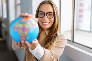 selbstbewusste junge frau mit brille hält einen globus in den händen